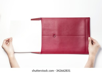 A woman(girl, female) hands hold(write) a luxury red leather envelope with a empty(blank, vacant, hollow) paper isolated white at the studio.