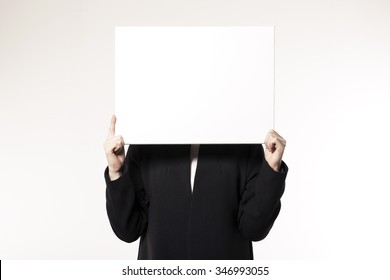 A woman(girl, female) wearing black coat and white shirts hand hold a empty(blank, vacant, hollow) white board(panel, canvas, paper) isolated white at the studio.
