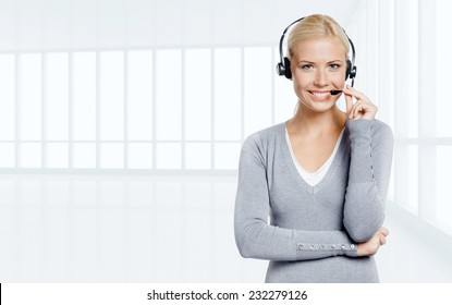 Woman-operator speaking on the microphone of the earphone in office