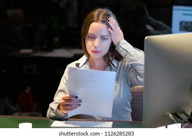 A woman-reception hotel worker reading negative news in letter. Shocked beauty girl business manager received layoff message letter from company feeling surprised. An agitated girl without joy.