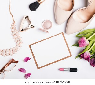 Woman's accessories of beige color, pink tulips and blank paper on white table, top view.