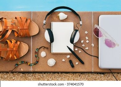 woman's accessories composed on floor at pool, still life, view from above, summer fashion trend, vacation, headphones, notebook, sunglasses, sandals, seashell, pen, travel diary, bracelet, flowers