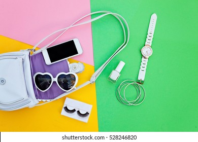 Woman's accessories lying flat on textured fabric background. yellow, green and pink pastel colors with copy space around products. Horizontal image or photograph.