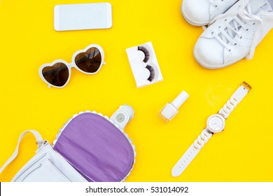 Woman's accessories lying flat on  yellow background. with copy space around products. Horizontal image or photograph.