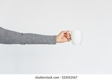 Woman's arm holding a cup of coffee