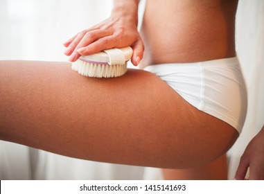 Woman's arm holding dry brush to top of her leg. Cellulite treatment, dry brushing