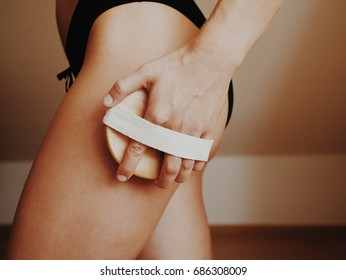 Woman's arm holding dry brush to top of her leg