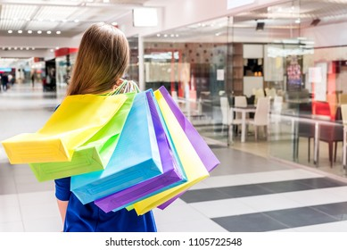 Woman's back with colorful packing bags over shoulder