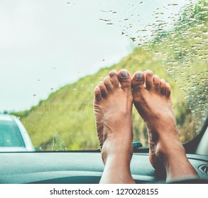Woman's bare foot on car dashboard at the road. Rain Drops on windshield. Freedom. Rustic
