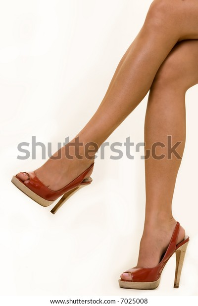 Woman's bare legs in red high heel shoes