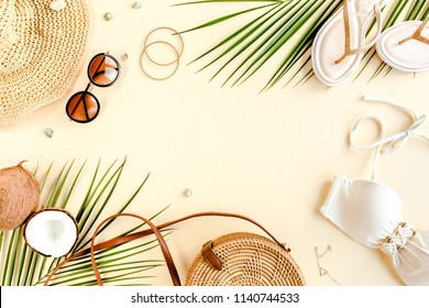 Woman's beach accessories: bikini, rattan bag, straw hat, tropical palm leaves on yellow background. Summer background. Flat lay, top view.