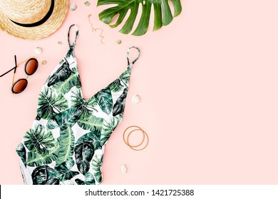 Woman's beach accessories: swimsuit with tropical print, straw hat on pink background. Summer background. Flat lay, top view.