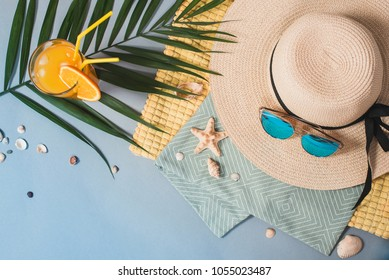 A woman's beach hat and blue sunglasses lie on a towel, next to a palm leaf, and seashells and a glass of cocktail on a blue background.