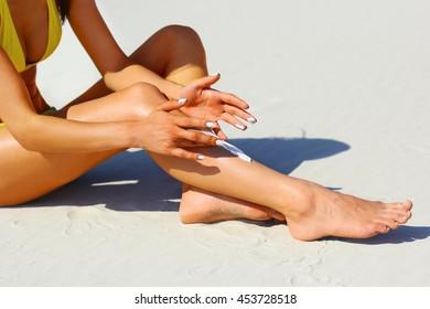 Woman's beautiful legs on the beach. Tan Woman Applying Sunscreen on Legs. Close-up