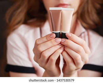 Woman's beauty blogger hands holding two tubes professional cosmetics, applying sample trendy tone on her skin with blurred body background warm cozy tones and copyspace