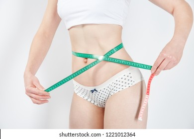 Woman's body after weight loss. Cropped close up photo of fatless slender body parts and proportions woman`s hands holding green centimeter measuring waistline isolated on background