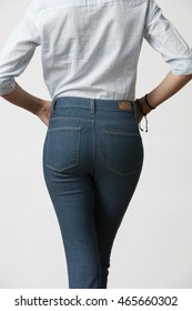 Woman's butt in slim fit jeans, on white background