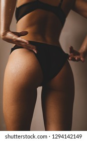 Woman's buttocks in underpants. Sexy woman in bikini. Fitness, diet and health. Skin health and body care. Woman in glitter and water drops is shining. Woman wear erotic underwear. Focus on haunch.