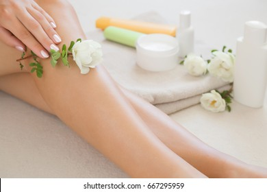Woman's cares about a soft skin with body creams, lotions or oils in the bathroom after shower and shaving. Fresh white rose's gentle touch and scent.