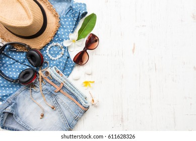 Woman's casual summer clothes with accessories items on white rustic wooden board background, overhead top view, flay lay