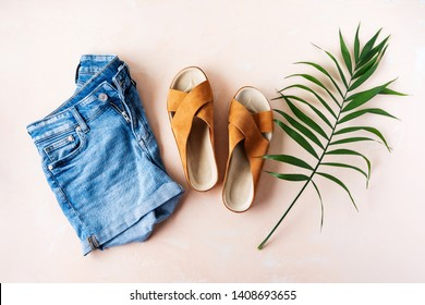 Woman's casual trendy leather sandals with crisscross details and denim shorts for summer vacation outfits on pink pastel background with palm leaf.