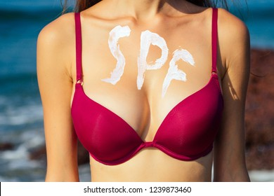 woman's chest in red swimsuit closeup against a tropical paradise beach and sea.spf and depilation shugaring epilation concept