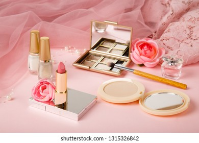 Woman's cosmetics on romantic pink lacy tulle background. Women's morning secrets. Cosmetics, lipstick,perfume, brush, powder, highlighter, concealer,patelle with eye shadows. Female cosmetics.Make up