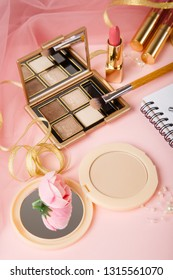 Woman's cosmetics on romantic pink lacy tulle background. Pink and golden colors. Lipstick, powder and eyeshadow. Romantic morning of woman. Female cosmetics. Make up