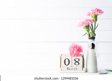 Womans day concept. Pink carnation flower in vase and red heart with March 8 text on wooden block calendar on white wooden background.