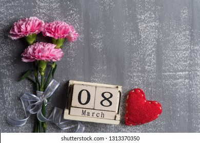 Womans day concept. Pink carnation flower with March 8 text on wooden block calendar and red heart and on gray wooden background.