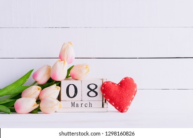 Womans day concept. Pink tulips and red heart with March 8 text on wooden block calendar on white wooden background.