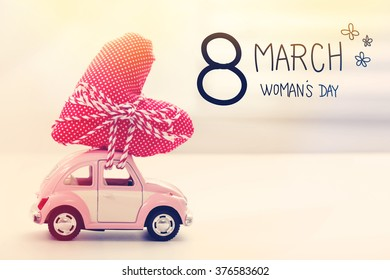 Womans Day message with miniature pink car carrying a heart cushion