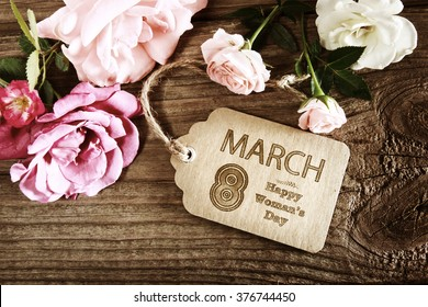 Womans Day message with rustic pink roses on wooden table