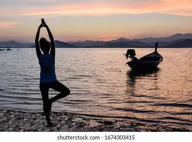 A woman's doing yoga on the beach