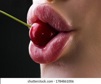 Womans enjoying a tests fresh sweet cherry. Female eating sweet cherry. Tasting food. Closeup female mouth tasting sweet cherry. Sweet enjoyment