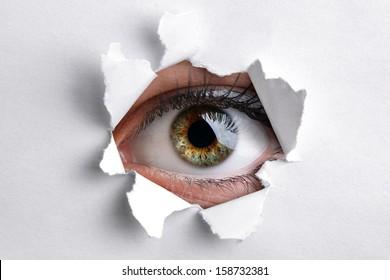 Womans eye peeking through a hole in white paper
