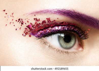 Woman's  eye with a shiny trendy makeup in violet tones with sparkles