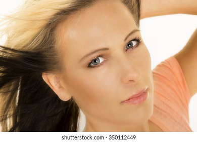A woman's face up close with the wind blowing.
