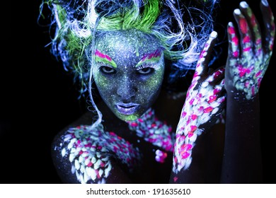 Woman's face with fluorescent body art. Black background.