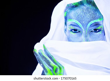 Woman's face with fluorescent bodyart. Black background.