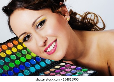 The woman's face in makeup on a background color palette of shadows
