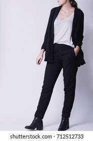 Woman's fall winter fashion outfit on a model with black smart cigarette trousers and white blouse or tshirt with black oversized blazer and black boots isolated on white background. Copy space.