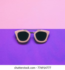 woman's fashionable sunglasses on pink and ultra violet background. tendy style. minimal. flat lay, top view.