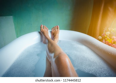 Woman's feet with foam bubble bath in luxury bathtub, Happiness and relaxing concept. -Vintage tone.