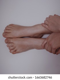 woman's feet with hands on white background