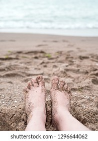 Woman's feet on the coarse sand near the sea. Relaxation at sea in countries with cold climates. Beach vacation holidays concept of freedom and travel. Close-up. Copy space. Travel lifestyle.