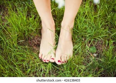 womans feet on green grass