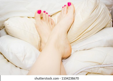 Woman's feet, up on the pile of soft pillows, bare with pink nail polish on toe nails