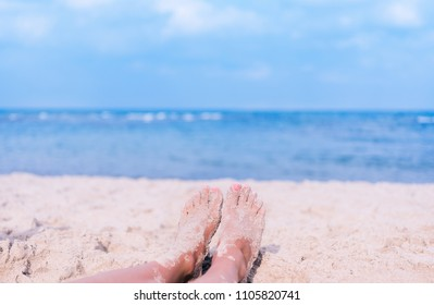 Woman's feet on sand with blue sea on background. Summer holiday vacation relaxation concept