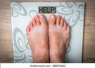 Woman's feet on a scale with word HELP! - obesity concept